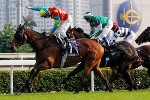 A delighted Zac Purton celebrates Ambitious Dragon's win in the Hong Kong Mile at Sha Tin on Sunday. Photo / AP