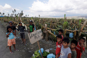 Residents affected by typhoon Bopha beg for aid from passing motorists along a highway in southern Philippines. Photo / AP