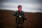A Free Syrian Army fighter takes position close to a military base, near Azaz, Syria. Photo / AP