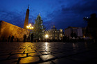 The cut-price Christmas tree is lit in St. Peter's square at the Vatican.
