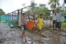 Twins Joen Soro and Mosikula Taitulo help remove the church furniture after the roof of Vusuya Methodist Church was blown off during the Tropical Cyclone Evans at Kuku. Photo / Jona Konataci/Fiji Sun