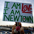 A Newtown, Conn., resident, who declined to give her name, sits at an intersection holding a sign for passing motorists up the road from the Sandy Hook Elementary School. Photo / AP
