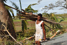 Cyclone Evan destroyed many homes in Nadi while in Lautoka a resident stocks up on newly created firewood. Photo / Fiji Ministry of Information