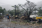 People walk through debris in Apia. Photo / AP