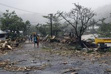 People walk through debris in Samoa's capital Apia. Photo / AP