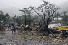 People walk through debris in Apia. Photo / AP