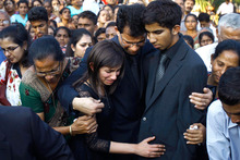 Husband Benedict Barboza, centre, holds his son Junal and daughter Lisha during the burial of Jacintha Saldanha. Photo / AP