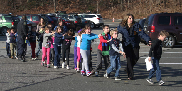 Connecticut State Police lead a line of children from the Sandy Hook Elementary School in Newtown. Photo / AP