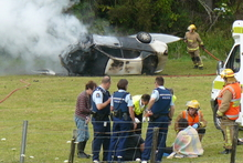 Kerikeri firefighters douse the crashed car while rescuer Mary Elliott (obscured) and emergency personnel comfort the children pulled from the wreckage. Photo / Supplied