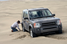 Dig out the sand around the wheels. A spade or shovel would be a lot better. Photo / Phil Hanson