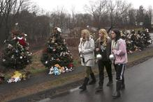 Mourners carry ornaments to decorate the Christmas trees at one of the makeshift memorials for the Sandy Hook Elementary School. Photo / AP 