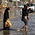 An Iraqi family make their way through flood water, after heavy rain fell in Baghdad, Iraq. Photo / AP