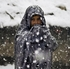 An Afghan internally displaced girl stands as snow falls at a refugee camp in Kabul, Afghanistan. Photo / AP