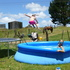 Olivia Laird flies into the pool on a hot summer's day at the farm in Hikurangi. Her sister Brooke is waiting for the splash. Photo / Sue Churton 