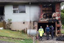 Police and fire officers investigate the scene of a suspicious house fire at Coburg St, Henderson. Photo / Richard Robinson