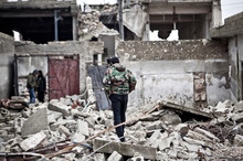 Free Syrian Army fighters walk amid the ruins of a village. Photo / AP