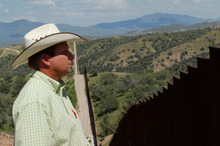 Rancher Dan Bell, who owns a 35,000-acre cattle ranch along the border between the United States and Mexico, looks at the imposing border fence, in Nogales, Arizona. Photo / AP