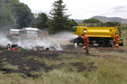 Central Otago Rural Fire Officers Ken Butcher (left) and Mark Davidson extinguish the last of the flames from a fire which destroyed the caravan. Photo / Lucy Ibbotson