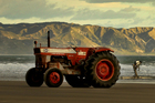 An old tractor and trailer await the return of a boat full of fishermen from an early morning trip off Waimarama Beach. Photo / Alan Gibson