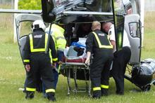 Jockey Ashlee Mundy is carried to the Otago Rescue Helicopter by emergency personnel after a race fall at Kurow yesterday. Photo / Otago Daily Times