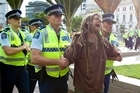 A protester is arrested by police as security staff and police remove Occupy Auckland from Aotea Square. Photo / Dean Purcell