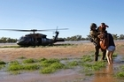 In this photo released by The Royal Australian Air Force, Warrant Officer Steve Carter, left, assists flood victims as they are evacuated. Photo / AP