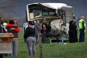 People comfort each other at the scene of an accident involving a school bus and a logging truck in the Ruatoki Valley, south of Whakatane in September. Photo / Alan Gibson