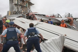 Police and volunteers work to rescue people trapped in the collapsed CTV building. Photo / Geoff Sloan