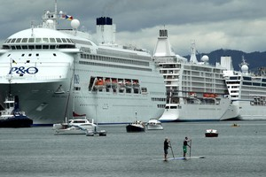Two paddle boarders are dwarfed by three cruise ships which  crowded into Tauranga Harbour yesterday - Pacific Jewel, Seven Seas Voyager and Regatta. Photo / Alan Gibson