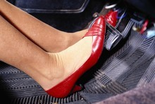 Flat shoes are best for driving, high heels are risky, and bare feet are inadvisable.