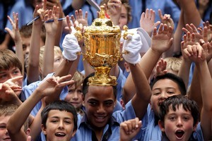 Lemeki Namoa  holds the Webb Ellis Cup as his fellow Year 8 and 9 students relive the excitement of last year's tournament. Photo / Sarah Ivey
