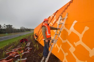 Artist Jeff Thompson fixing his artwork to the noise wall at Brighams Creek Rd. Photo / Paul Estcourt