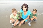 Robin Broadstock, Fiona Bryant and Keanu Sadlier with a packet of egg fried rice coated in a sticky oil-like substance that she found on Turihaua Beach with her nephew. Photo / Gisborne Herald