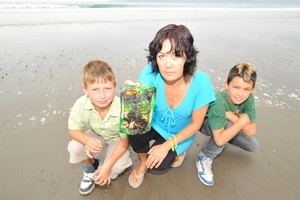 Robin Broadstock, Fiona Bryant and Keanu Sadlier with a packet of egg fried rice coated in a sticky oil-like substance that she found on Turihaua Beach with her nephew. Photo / Dave Thomas