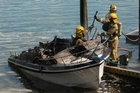 Fire crews bring the burned-out boat up to the ferry wharf. Photo / Greg Bowker