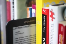 Conventional books sandwich a Kindle 3G electronic book reader. Picture / Bloomberg