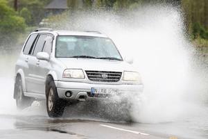 A car drives through flood waters in Pitt Town near Richmond, Australia. Photo / Getty Images