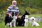 Mike Butler with his three dogs - and a playmate pooch. 'It's horrendous.' Photo / Marty Melville