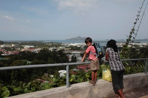 A woman and child stop view the panorama around the Victoria's harbor skyline in the Seychelles Island. Photo / AP
