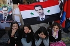 Syrian women sit under a Syrian flag with a portrait of Syrian President Bashar Assad, outside a polling station during a referendum on the new constitution. Photo / AP
