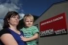 Jodi Condin from Taradale, Napier, with her son Toby Condin, 3, are not impressed with the new signage at Equippers church in Tamatea Napier which claims Jesus heals cancer. Photo / APN