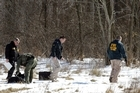 FBI and local police investigators search for evidence in a rural area of Chardon Township following the shooting. Photo / AP