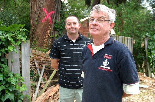 ILL WINDS: Featherston fire chief Colin McKenna (right) and senior station officer Lee McKenna stand among some of the debris that blocked access to Kereru Grove in Featherston yesterday after 100km/h gales tore branches from a large gum tree.