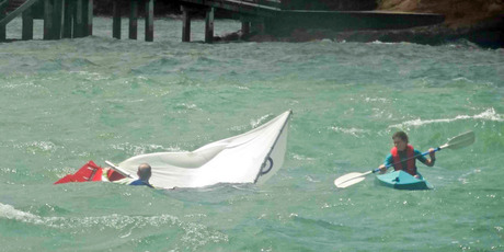 A kayaker goes to the aid of a sailor who capsized off Island Bay, North Shore yesterday. The Coastguard came to the rescue shortly after this picture was taken. Photo / Owen Blackburn