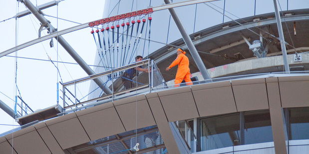 A man is spoken to by police on the 54th floor of Auckland's Sky Tower. Photo / Michael Craig
