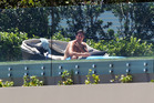 A sunbather enjoys the pool at the home of failed financier Mark Hotchin. Photo / Doug Sherring