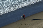 A surfer walks along Ngarunui (Ocean) Beach in Raglan as the sun sinks low on the horizon. Photo / Alan Gibson