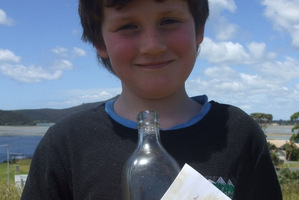 Shayde Flood with the bottle that washed up on 90 Mile Beach. Photo / Supplied