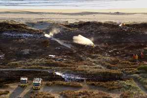 Firemen dampen down a grass fire near the Ocean Beach surf lifesaving club, Ocean Beach. Photo / Warren Buckland