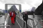 Milford Track trampers arrive back safely at Milford Sound yesterday after experiencing some of worst flooding seen on the track for years. Photo / Olivia Caldwell